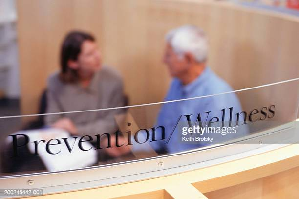 Prevention/wellness sign, Woman providing man with information about prostate in background