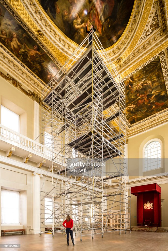 Preventive conservation co-ordinator at Historic Royal Palaces Jonathan Bridal (on top) inspects the Rubens ceiling paintings for damage during a conditioning survey at Banqueting House on January 21, 2014 in London, England. Flemish artist Sir Peter Paul Rubens painted the nine oil canvases for Charles I, they were installed in the hall in 1636. The three main canvasses depict The Union of the Crowns, The Apotheosis of James I and The Peaceful Reign of James I, since their creation, the paintings have undergone at least 14 restoration treatments including mounting the canvases permanently onto plywood boards in 1907. For the first time Historic Royal Palaces has taken paint samples of the coffering to determine past colour schemes.