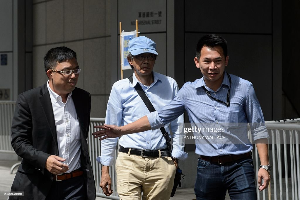 Previously missing bookseller Lam Wing-Kee (C) arrives outside Wanchai police station with local lawmaker James To (L) in Hong Kong on June 29, 2016. China agreed on June 27 to talks with Hong Kong in the wake of explosive revelations by a city bookseller who said he was detained for eight months on the mainland, as fears grow that Beijing is tightening its grip. / AFP / ANTHONY