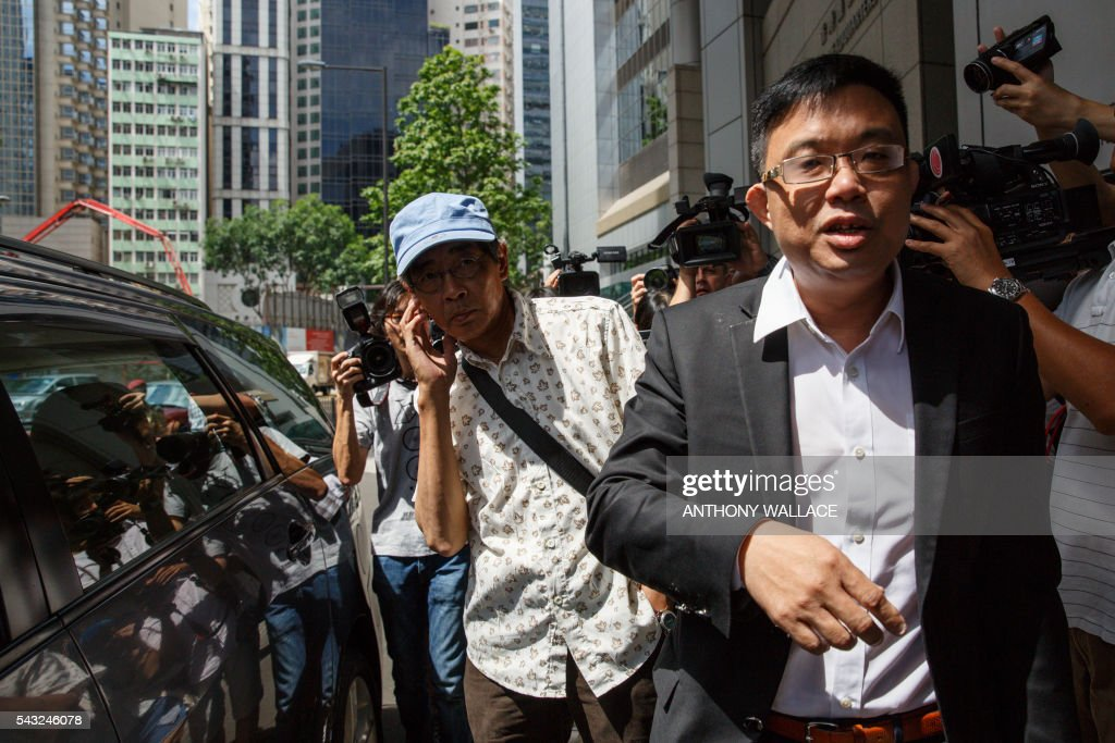 Previously missing Hong Kong bookseller Lam Wing-kee (L) arrives at Wanchai police station with local lawmaker James To (R) to report to the police in Hong Kong on June 27, 2016. Lam is one of five city booksellers known for selling gossipy titles about Beijing politicians who have disappeared and later resurfaced in China. Lam claimed he was kept in a cell, blindfolded and interrogated. / AFP / ANTHONY