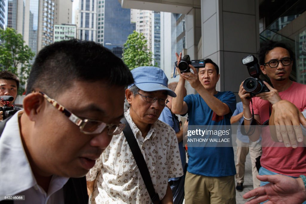 Previously missing Hong Kong bookseller Lam Wing-kee (C-in hat) arrives at Wanchai police station with local lawmaker James To (L) to report to the police in Hong Kong on June 27, 2016. Lam is one of five city booksellers known for selling gossipy titles about Beijing politicians who have disappeared and later resurfaced in China. Lam claimed he was kept in a cell, blindfolded and interrogated. / AFP / ANTHONY