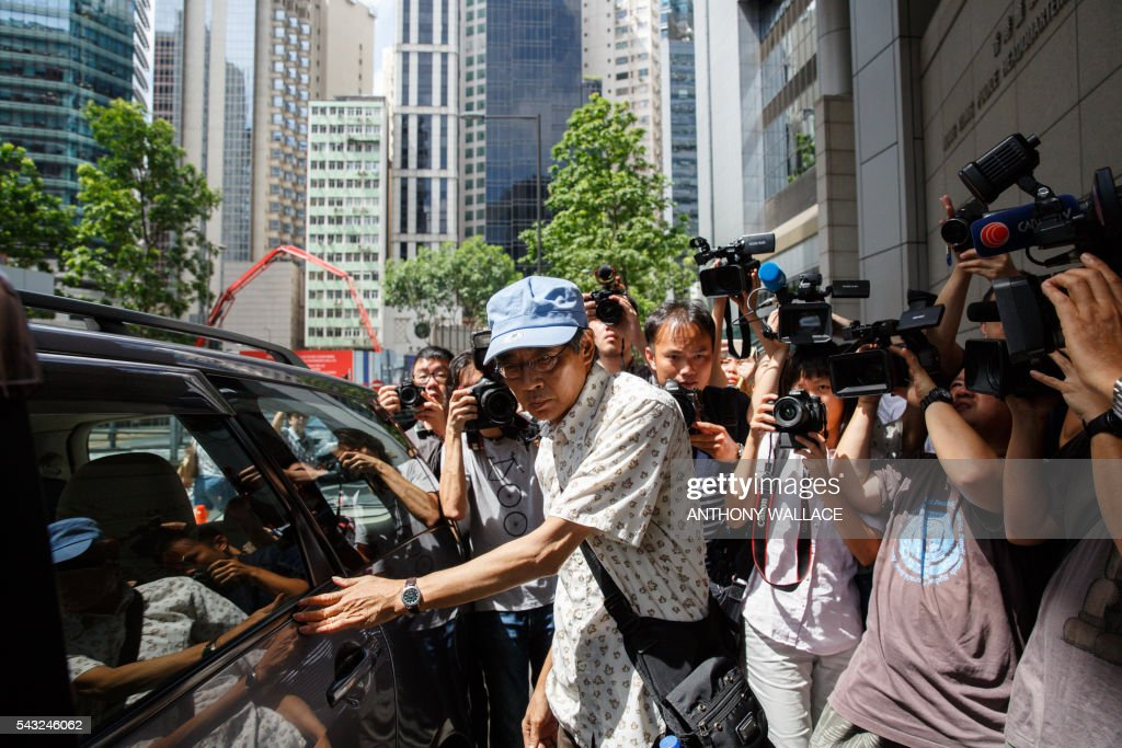 Previously missing Hong Kong bookseller Lam Wing-kee (C) arrives at Wanchai police station to report to the police in Hong Kong on June 27, 2016. Lam is one of five city booksellers known for selling gossipy titles about Beijing politicians who have disappeared and later resurfaced in China. Lam claimed he was kept in a cell, blindfolded and interrogated. / AFP / ANTHONY