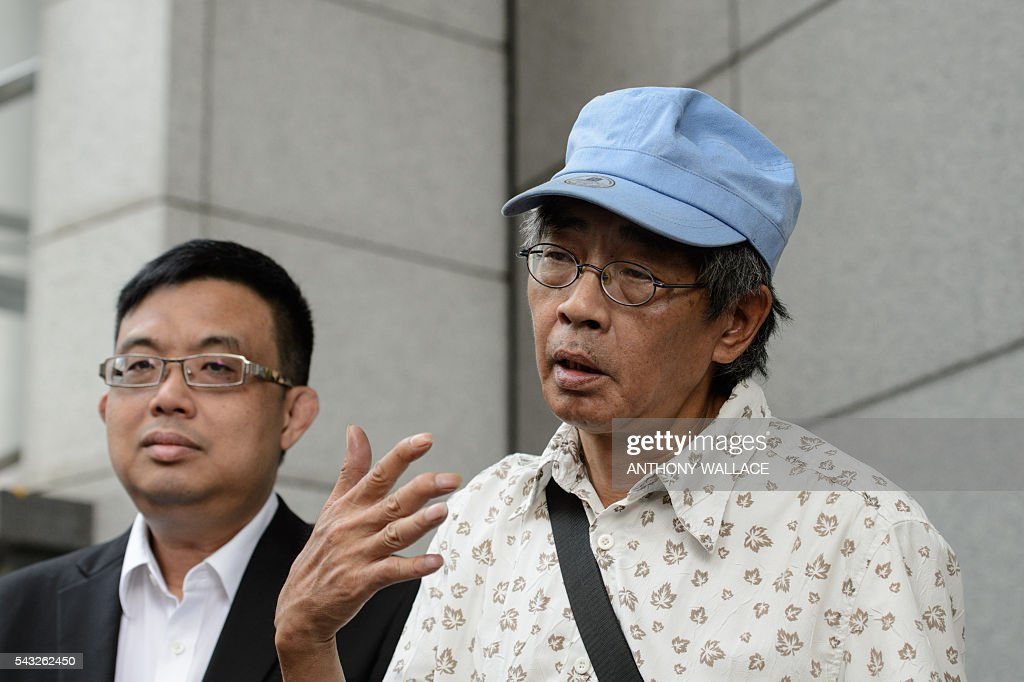 Previously missing Hong Kong bookseller Lam Wing-kee (C) gestures as he speaks during a press conference outside Wanchai police station after reporting to the police with local lawmaker James To (L) in Hong Kong on June 27, 2016. Lam is one of five city booksellers known for selling gossipy titles about Beijing politicians who have disappeared and later resurfaced in China. He claimed he was kept in a cell, blindfolded and interrogated. / AFP / ANTHONY