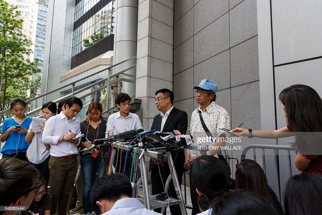 Previously missing Hong Kong bookseller Lam Wing-kee (centre R, blue cap) holds a press conference outside Wanchai police station after reporting to the police with local lawmaker James To (C) in Hong Kong on June 27, 2016. Lam is one of five city booksellers known for selling gossipy titles about Beijing politicians who have disappeared and later resurfaced in China. He claimed he was kept in a cell, blindfolded and interrogated. / AFP / ANTHONY