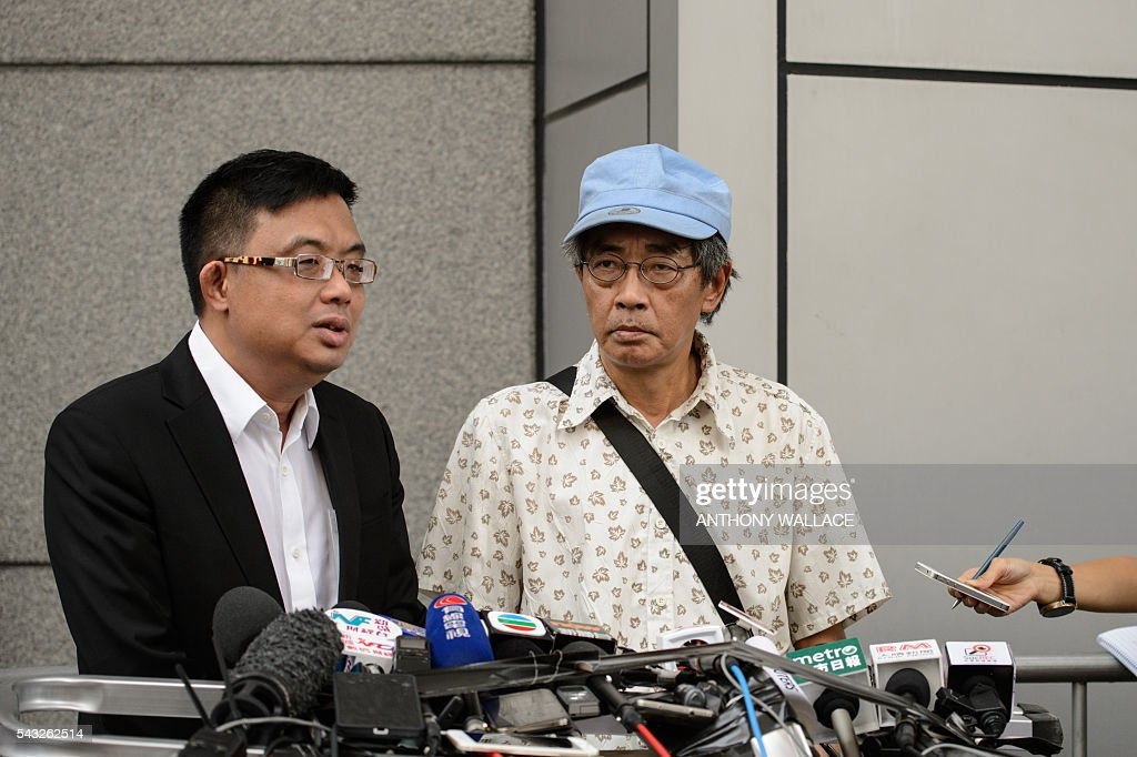 Previously missing Hong Kong bookseller Lam Wing-kee (C) holds a press conference outside Wanchai police station after reporting to the police with local lawmaker James To (L) in Hong Kong on June 27, 2016. Lam is one of five city booksellers known for selling gossipy titles about Beijing politicians who have disappeared and later resurfaced in China. He claimed he was kept in a cell, blindfolded and interrogated. / AFP / ANTHONY