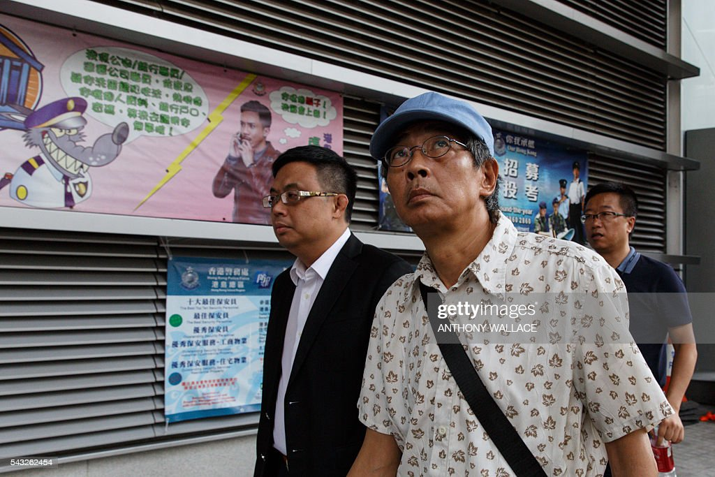 Previously missing Hong Kong bookseller Lam Wing-kee (2nd R, blue cap) leaves Wanchai police station after reporting to the police with local lawmaker James To (L) in Hong Kong on June 27, 2016. Lam is one of five city booksellers known for selling gossipy titles about Beijing politicians who have disappeared and later resurfaced in China. He claimed he was kept in a cell, blindfolded and interrogated. / AFP / ANTHONY