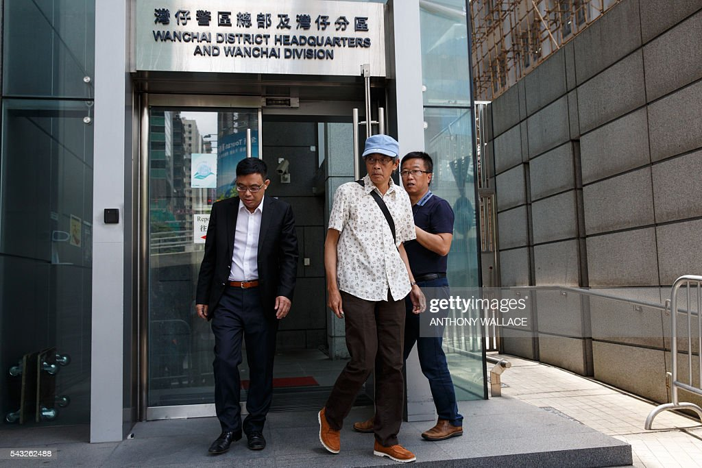 Previously missing Hong Kong bookseller Lam Wing-kee (C, blue cap) leaves Wanchai police station after reporting to the police with local lawmaker James To (L) in Hong Kong on June 27, 2016. Lam is one of five city booksellers known for selling gossipy titles about Beijing politicians who have disappeared and later resurfaced in China. He claimed he was kept in a cell, blindfolded and interrogated. / AFP / ANTHONY