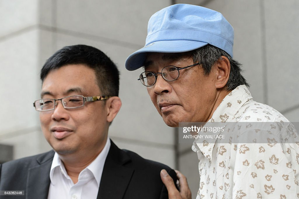 Previously missing Hong Kong bookseller Lam Wing-kee (C) places his hand on the shoulder of local lawmaker James To (L) during a press conference held outside Wanchai police station after Lam reported to the police in Hong Kong on June 27, 2016. Lam is one of five city booksellers known for selling gossipy titles about Beijing politicians who have disappeared and later resurfaced in China. He claimed he was kept in a cell, blindfolded and interrogated. / AFP / ANTHONY
