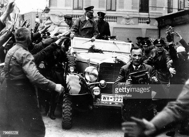 PreWorld War II 14th March 1938 Linz Austria German Chancellor and Nazi leader Adolf Hitler stands in his car as he is driven triumphantly through...