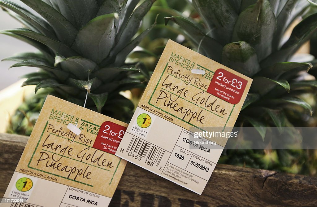 Price tags are seen attached to pineapples inside a Marks & Spencer Group Plc (M&S) food hall in the Westfield Stratford City retail complex in London, U.K., on Thursday, June 27, 2013. U.K. retail sales rose more than economists forecast in May as consumers spent more online and food sales increased at their fastest pace for more than two years. Photographer: Chris Ratcliffe/Bloomberg via Getty Images