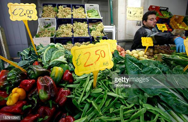 Prices in euro denominations are seen on tags sitting among fruit and vegetables on a market stall at an indoor market in downtown Rome Italy on...