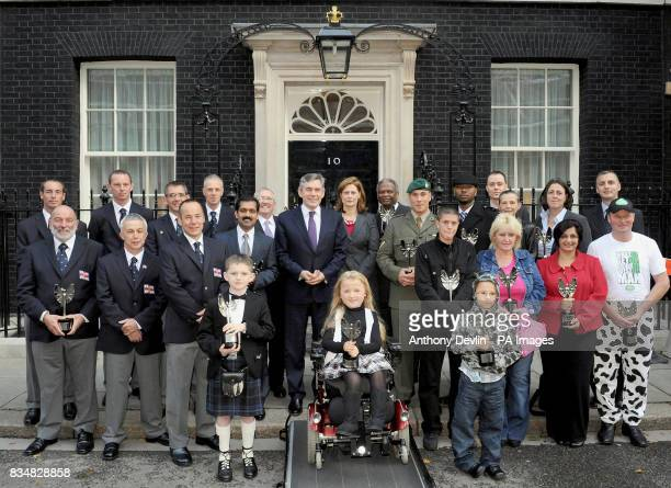 Pride of Britain winners pose with Prime Minister Gordon Brown and wife Sarah outside Downing Street London following the awards ceremony last night