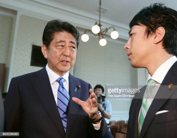 Prie Minister and ruling Liberal Democratic Party President Shinzo Abe talks to Shinjiro Koizumi after the party's lawmakers meeting at the party...