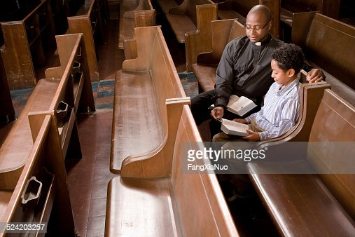 Priest and Boy in Church Pew Reading Bible