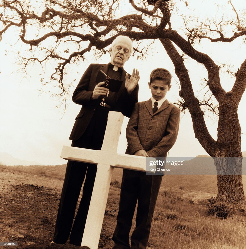 Priest and boy (8-10) praying by grave (sepia tone) : Stock Photo