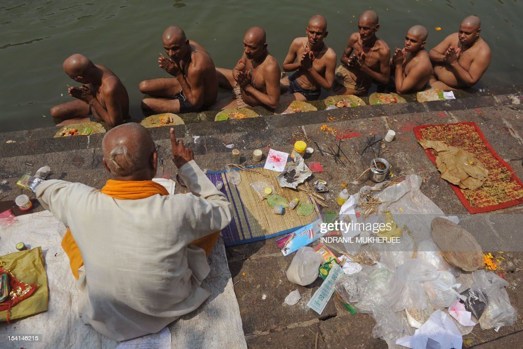 A priest assists Indian Hindu devotees perform 'Tarpan', a ritual to pay obesience to one's forefathers, on the last day for offering prayers to ancestors called 'Pitrupaksh' in Mumbai on October 15, 2011. In Hindu mythology, this day is also called 'Mahalaya' and described as the day when the gods created the ten armed goddess Durga to destroy the demon king Asura who plotted to drive out the gods from their kingdom. The five-day period of worship of Durga, who is attributed as the destroyer of evil, commences on October 20. AFP PHOTO/Indranil MUKHERJEE