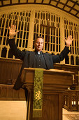 Priest at podium with arms raised
