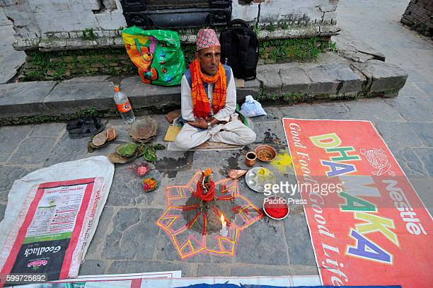 Priest awaits for the devotees to offering ritual prayer at the Bank of Bagmati River of Pashupatinath Temple during Rishi Panchami Festival...