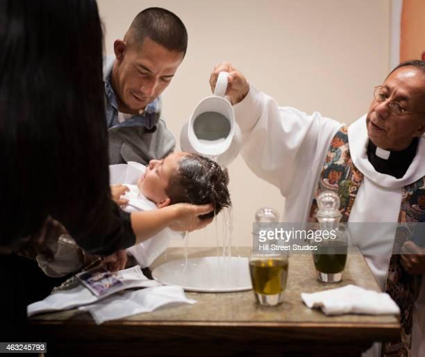 Priest baptizing boy in church