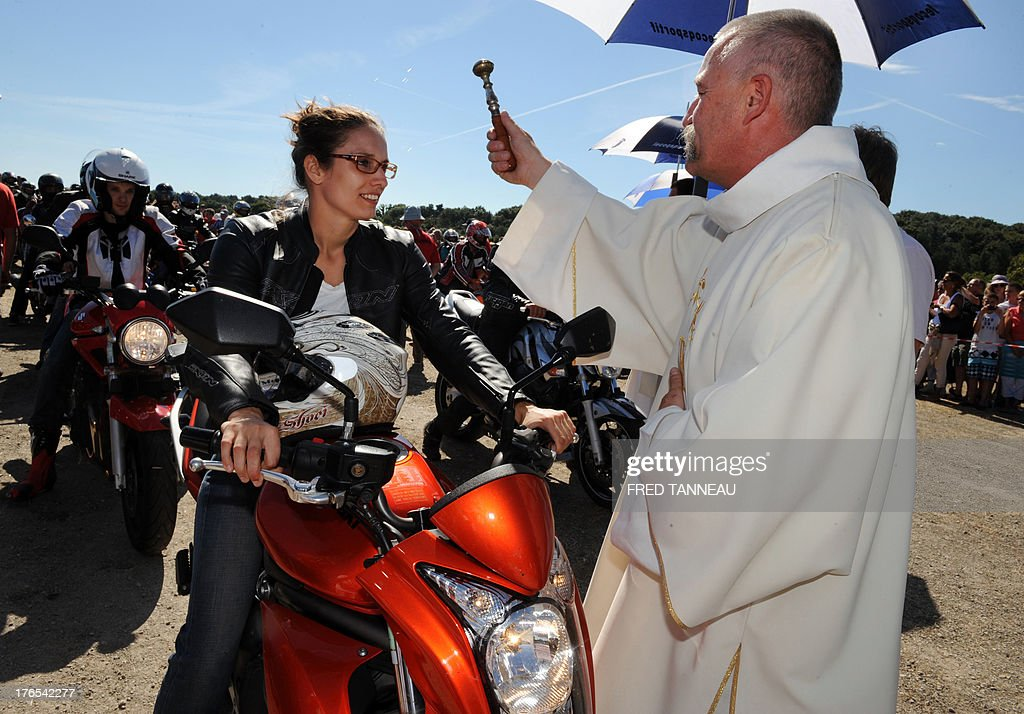 A priest blesses a motorbiker on August 15, 2013 in Porcaro, western of France, during the traditional motorbike pardon on Assumption Day.