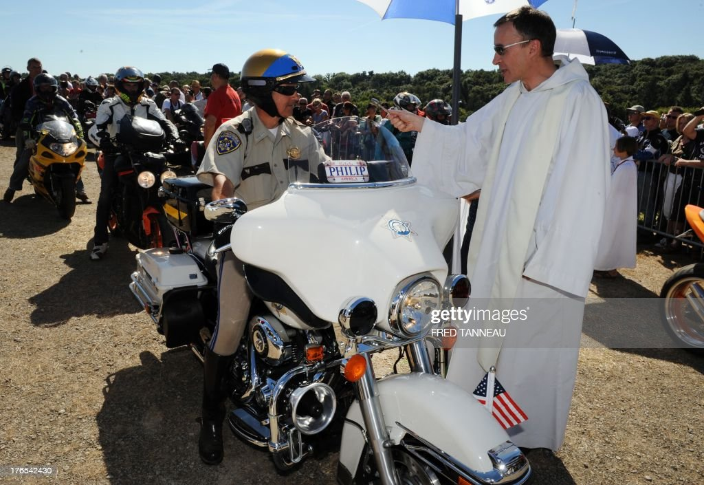 A priest blesses a motorbiker on August 15, 2013 in Porcaro, western of France, during the traditional motorbike pardon on Assumption Day. AFP PHOTO FRED TANNEAU