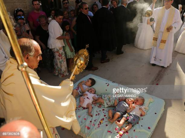 A priest blesses babies during 'El Colacho' the 'baby jumping festival' in the village of Castrillo de Murcia near Burgos on June 18 2017 Baby...