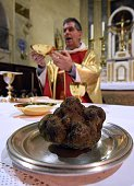 A priest blesses black truffles during a mass to bless and celebrate the truffle at a church in Uzes southern France on January 18 2015 The truffle...
