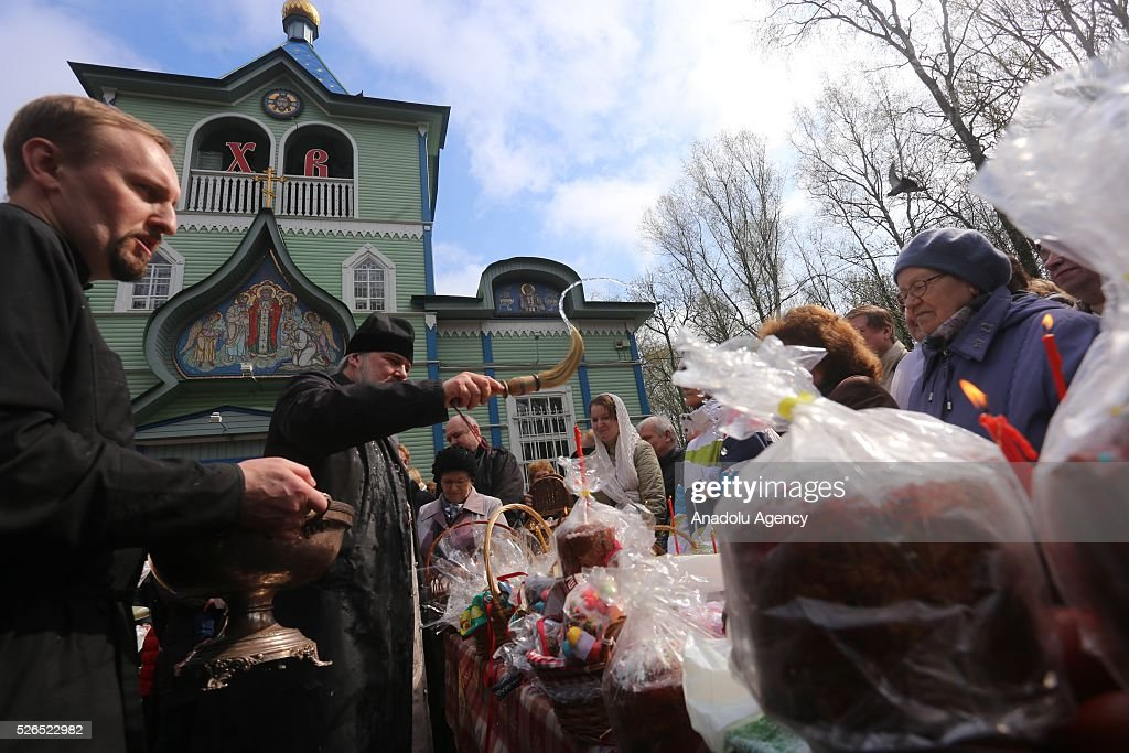 A priest blesses Easter cakes (kulichs), eggs and believers on Orthodox Holy Saturday at a church in Saint-Petersburg, Russia on April 29, 2016.