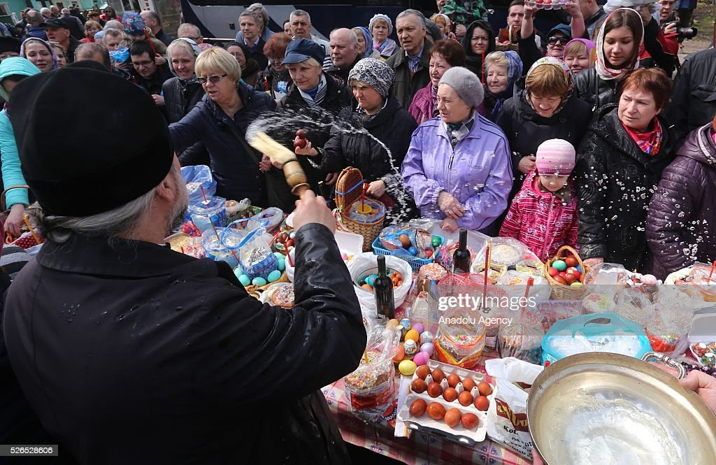 A priest blesses Easter cakes (kulichs), eggs and believers on Orthodox Holy Saturday at a church in Saint-Petersburg , Russia on April 29, 2016.