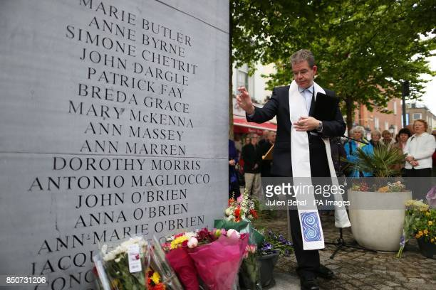 A priest blesses the flowers during the annual wreath laying and memorial service for1974 the Dublin/Monaghan bombings victims at the monument to the...