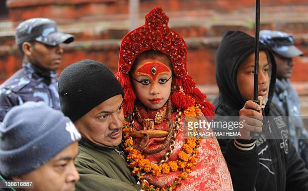 A priest carries Nepalese living goddess Kumari Mateena Shakya towards The Taleju Temple in Kathmandu on January 9 on the occassion of the Changu...