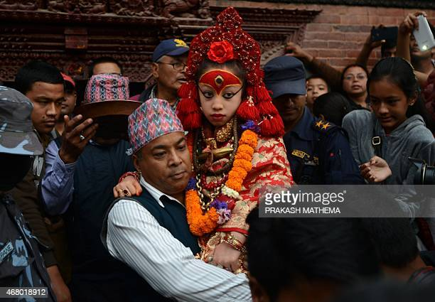 A priest carries Nepal's Living Goddess 'Kumari Devi' to watch a procession on the third day of the Seto Machindranath chariot festival in Kathmandu...