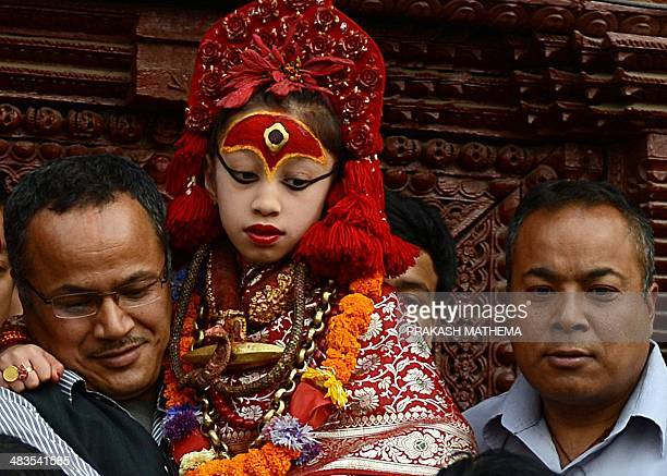 A priest carries Nepal's Living Goddess 'Kumari Devi' to watch the a procession on the last day of the Seto Machindranath chariot festival in...