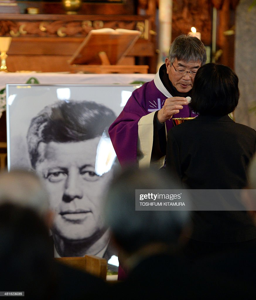 Priest Eiji Tanaka (2nd R) leads the mass in honour of former US president John F. Kennedy on the 50th anniversary of his assassination at his San-no Cho Catholic Toyama church in Toyama on November 23, 2013. About 100 followers in different religions gathered to mourn the late US president. AFP PHOTO / TOSHIFUMI KITAMURA