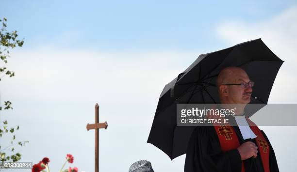 A priest follows the final mass of the Kirchentag festival celebrating the 500th anniversary of the Reformation at a meadow near the river Elbe near...