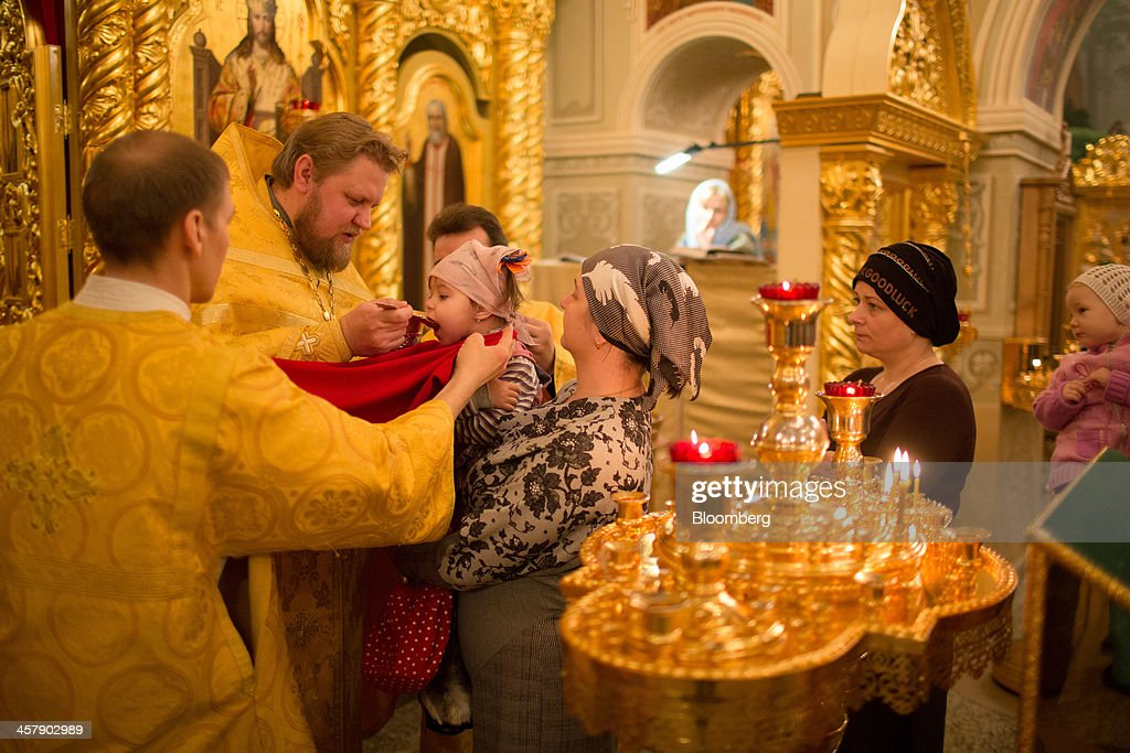 A priest gives a child holy communion during a Sunday service inside the orthodox church of Saint Seraphim of Sarov in the mining town of Udachny, Sakha Republic, Russia, on Sunday, Dec. 15, 2013. Russia plans to maintain control of Mirny-based Alrosa, which produces a quarter of the world's diamonds by value and more rough diamonds than De Beers by carat. Photographer: Andrey Rudakov/Bloomberg via Getty Images