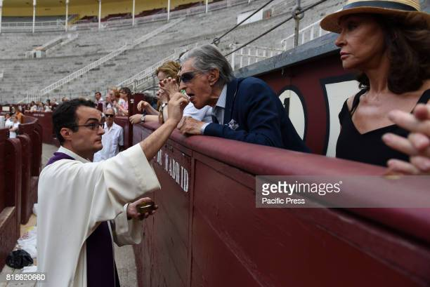 A priest gives communion to Spanish exbullfighter Jaime Ostos during a funeral mass for Spanish bullfighter Ivan Fandiño who died after being gored...