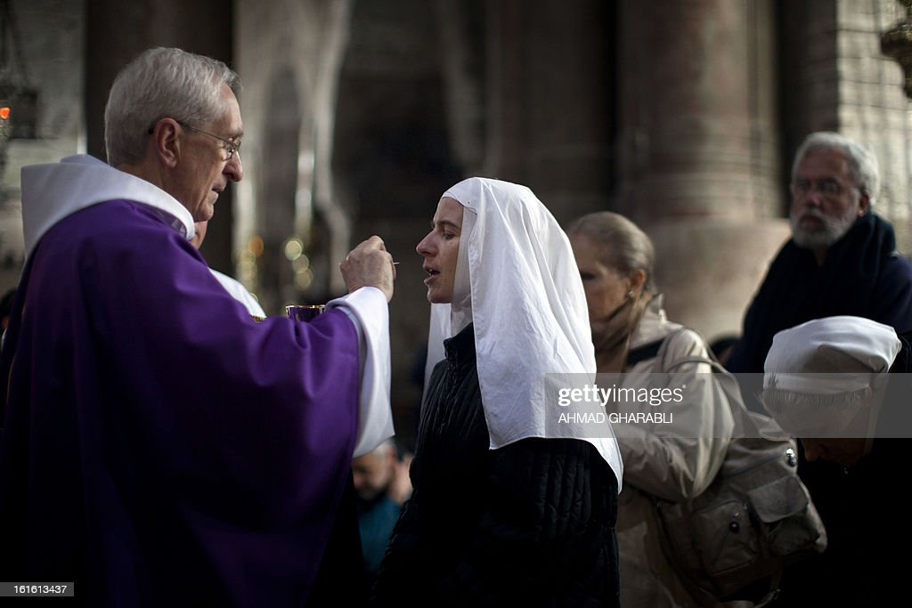A priest gives holy communion to a nun during mass at a church Holy Sepulcher in Jerusalem's Old City to mark Ash Wednesday, which launches the traditional period of penitence ahead of Easter in the Christian calendar, on February 13, 2013. The Catholic Church faced a tricky transition on Tuesday as it prepared to elect a new pope, with many faithful still reeling from the shock resignation of Pope Benedict XVI. AFP PHOTO/AHMAD GHARABLI