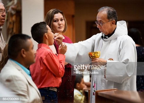 Priest giving communion during mass in Catholic church