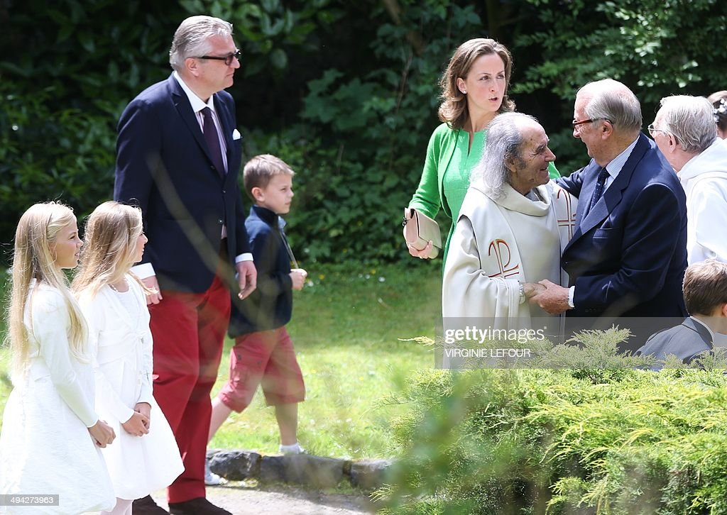 Priest Guy Gilbert (2nd R) embraces King Albert II of Belgium (R) beside to Prince Laurent of Belgium (3rd L) and Princess Claire of Belgium (C), after the celebration of the first communion of twin Princes Nicolas and Aymeric at the Sainte-Catherine church, on May 29, 2014, in Bonlez.