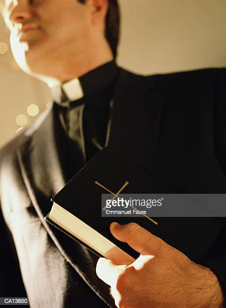 Priest holding bible, close-up, low angle view