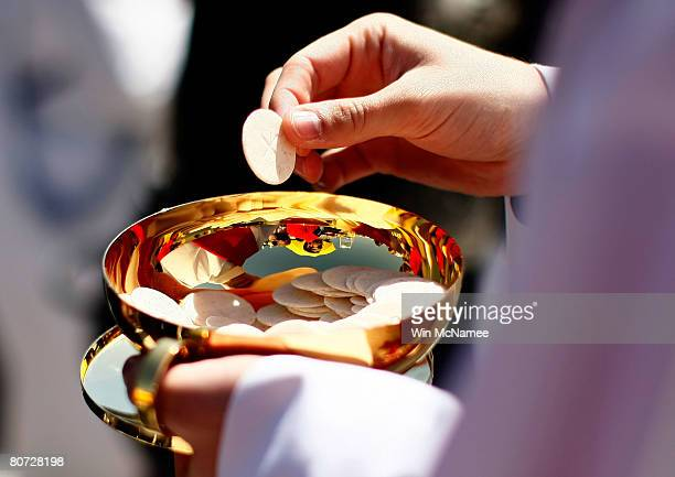 A priest holds a Holy Communion wafer as Pope Benedict XVI celebrates Mass at Nationals Park April 17 2008 in Washington DC Today is Pope Benedict...