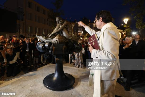 Priest Jean Paul Gouarin is watched by onlookers including Italian artist Milo Manara as he blesses a statue of French actress Brigitte Bardot during...