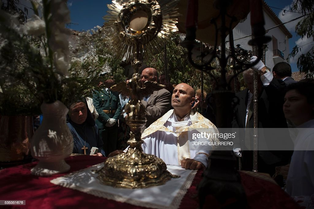 A priest kneels to pray in front of an altar during the Corpus Christi celebrations in El Gastor, southern Spain on May 29, 2016. The village of El Gastor celebrate the feast of Corpus Christi (or Body of Christ in Latin) covering the streets and facades of houses with branches of trees and grass. / AFP / JORGE