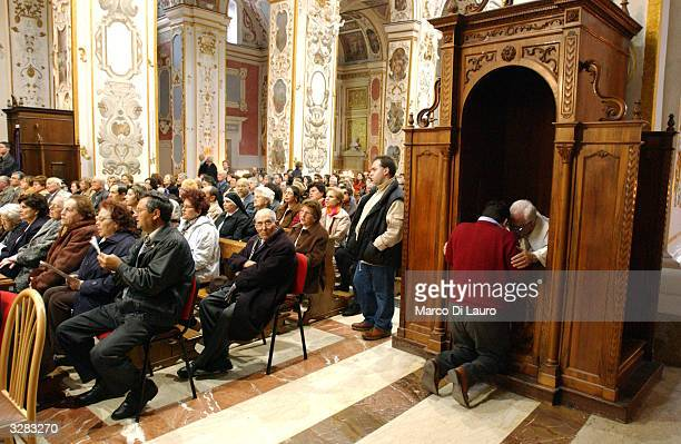 A priest listens to confession during a ceremony where the bishop will attend the rite of the washing of the feet in the cathedral before the...