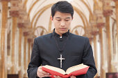 Priest Looking at Bible in a Church