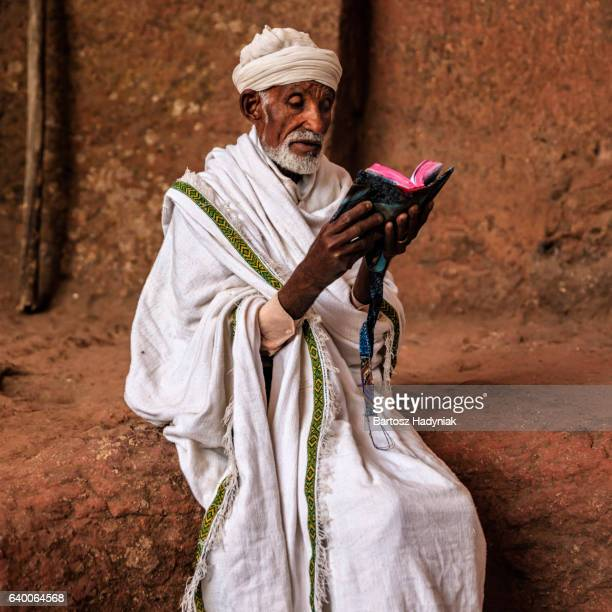 Priest of rock-hewn church reading holy book, Lalibela