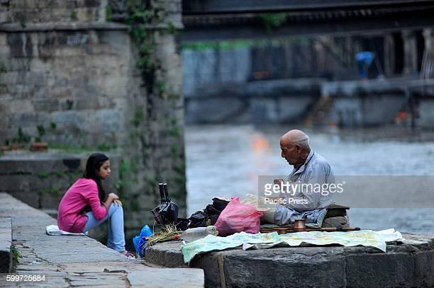 Priest offering ritual prayer at the Bank of Bagmati River of Pashupatinath Temple during Rishi Panchami Festival celebrations at Pashupatinath...