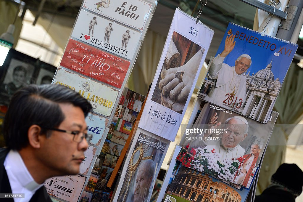 A priest passes by a newstand where calendars showing Pope Benedict XVI (top-R) and John Paul II are displayed on February 15, 2013 in Rome. Pope Benedict XVI the day before called for 'real renewal' in the Church at an emotional farewell with priests from his Rome diocese where he said he would be 'hidden from the world' once he resigns.