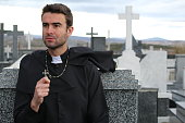 Priest performing an exorcism in a windy cemetery.